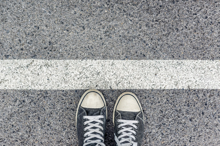 Man standing at the border line on urban pavement, top view of young male feet wearing sneakers, waiting behind the line, immigration concept