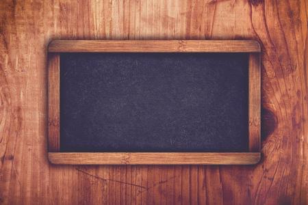 space wood: Retro toned empty chalkboard as copy space on rustic oak wood plank texture.