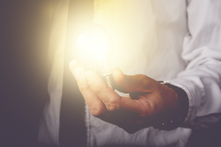 ingenious: Business idea and vision, businessman holding light bulb, concept of new ideas, innovation, invention and creativity, retro toned image, selective focus. Stock Photo