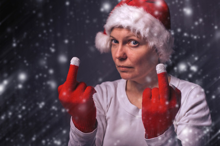middle finger: Beautiful woman in Santa Claus costume giving middle finger, selective focus. Stock Photo