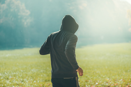 Hooded man jogging in the park in early autumn morning, sport, recreation and healthy lifestyle concept, retro toned image with selective focus Banque d'images
