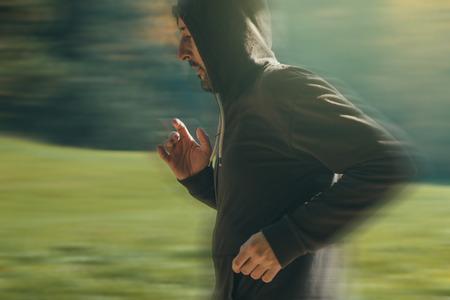 panning shot: Uomo incappucciato jogging nel parco di inizio autunno mattina, lo sport, la ricreazione e il concetto di stile di vita sano, immagine retr� tonica, panning tiro con messa a fuoco selettiva