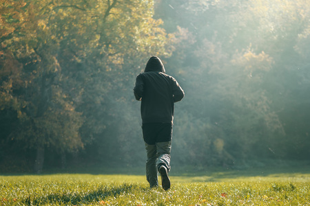 morning: Hooded man jogging in the park in early autumn morning, sport, recreation and healthy lifestyle concept, retro toned image with selective focus Stock Photo