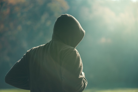 early: Hooded man jogging in the park in early autumn morning, sport, recreation and healthy lifestyle concept, retro toned image with selective focus Stock Photo