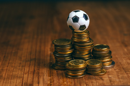 Soccer bet concept with small football on top of coin stack, making money by predicting sport results. Stockfoto