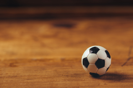 truncated: Miniature plastic soccer ball on wooden table with copy space, retro toned selective focus Stock Photo