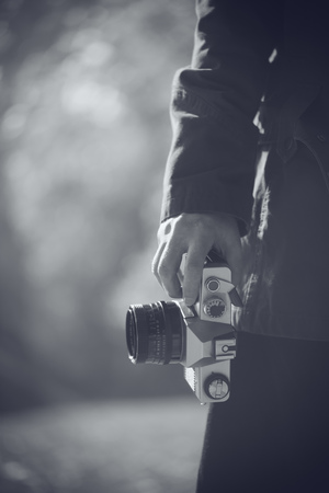photo pictures: Hipster female photographer exploring autumn nature landscapes and taking pictures of beautiful season scenery with old vintage film SLR camera, retro toned black and white image with selective focus on hand holding photo equipment. Stock Photo