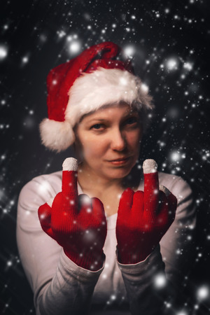 nothing: Nothing for Christmas, beautiful woman in Santa Claus costume showing rude middle finger hand sign, retro toned, selective focus. Stock Photo