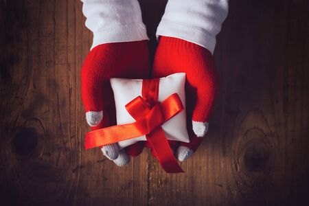 giftware: Christmas eve gift, hands giving wrapped present, top view retro toned image with selective focus
