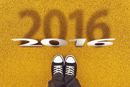 top year: Happy New Year 2016 with Person Wearing Black Sneakers from Above, Top View