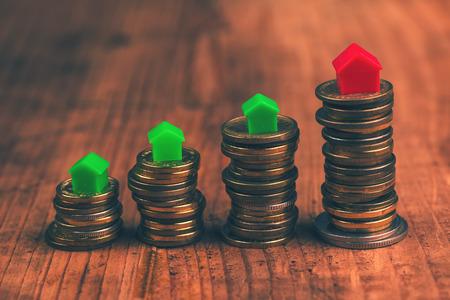 Hypotheek concept met kleine plastic huis modellen op de top van gestapelde munten. Stockfoto