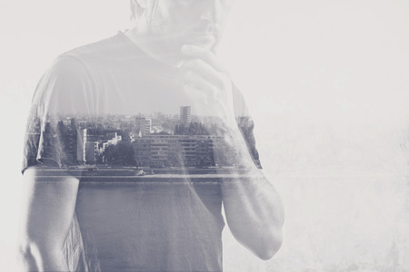 reconsider: Double exposure of man thinking with hand on chin, cityscape in background. Stock Photo