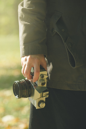 photo pictures: Female photographer exploring autumn nature landscapes and taking pictures of beautiful season scenery with old generic vintage film camera, retro toned image with selective focus on hand holding photo equipment. Stock Photo