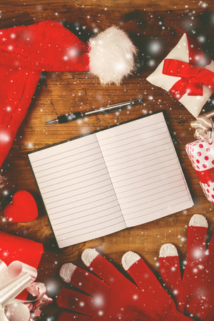 christmas list: Santa Claus work desk, empty notebook as copy space for good children wish list, hat and gloves with Christmas gifts and presents, top view