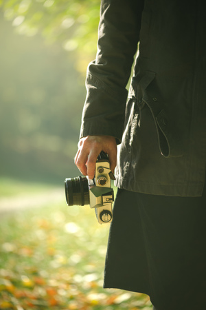 nature photo: Hipster female photographer exploring autumn naturescenery and capturing photos of beautiful season scenery with old vintage film camera, retro toned image with selective focus on hand holding photo equipment. Stock Photo