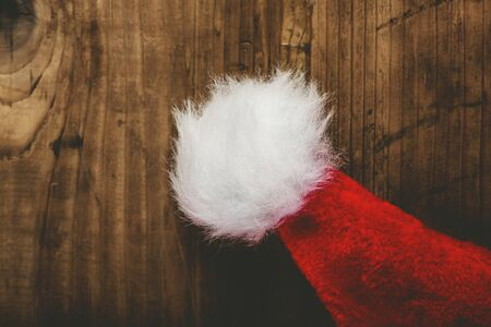 santa cap: Retro toned Santa Claus hat on wooden desk with blank copy space, top view