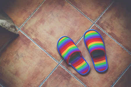 sexual orientation: Retro toned rainbow color pattern slippers on ceramic tiled floor with natural daylight from the window, LGBT pride and coming out of closet concept, top view Stock Photo