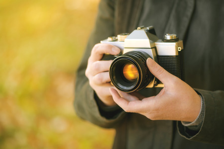 old hand: Hipster female photographer shooting outdoors, exploring autumn nature landscapes and taking pictures of beautiful season scenery with old vintage film camera, retro toned image with selective focus on hand holding photo equipment. Stock Photo