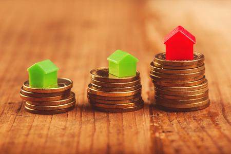 누적 된 동전의 상단에 작은 플라스틱 집 모델 부동산 모기지 개념.