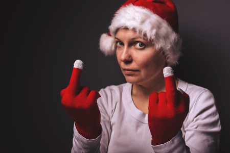 middle finger: Beautiful woman in Santa Claus costume showing middle finger, female gving rude hand sign, vulgar gesturing, selective focus.