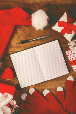 papier a lettre: Santa Claus work desk, empty notebook as copy space for good children wish list, hat and gloves with Christmas gifts and presents, top view