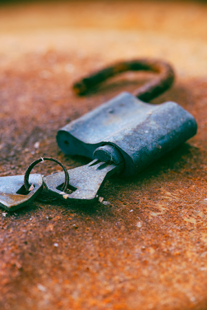 oxidize: Old padlock and keys on rusty background, selective focus Stock Photo