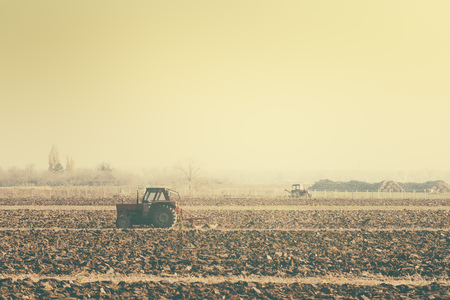 field crop: Retro toned tractors on arable field, agricultural machinery plowing the land