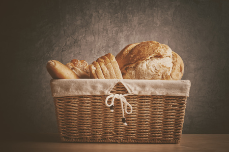Retro toned bread in wicker basket on kitchen table Stock Photo