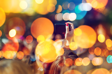 snapshot: Fans taking pictures of music band performing live on festival stage, female hand holding compact photography camera making snapshot photo of staged event, selective focus with bokeh light