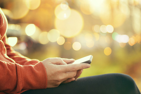 mobile sms: Casual woman using mobile smartphone outdoors, retro toned close up image with selective focus and bokeh light background