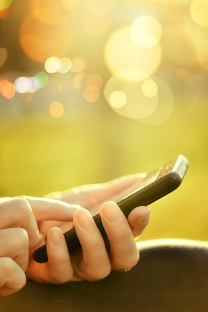 lady on phone: Casual woman using mobile smartphone outdoors, retro toned close up image with selective focus and bokeh light background
