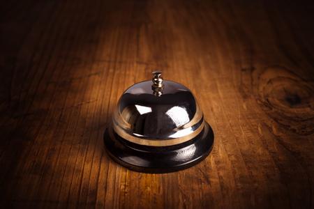 campanas: Hotel de llamada de servicio de campana en la recepci�n de recepci�n de madera, en tonos retro imagen. Foto de archivo
