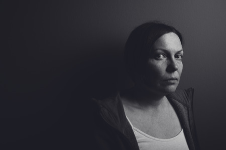 intense: Intense low key portrait of pensive sad woman leaning on gray room wall, low contrast monochromatic image Stock Photo