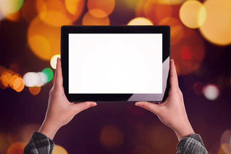 blank tablet: Woman with blank screen digital tablet computer as copy space, bokeh street light in background.