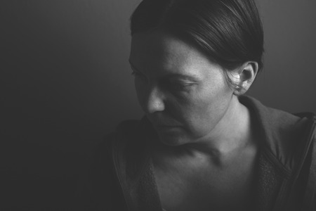 Depressive woman, low key monochromatic portrait of sad adult female in dark room Stok Fotoğraf - 49188040