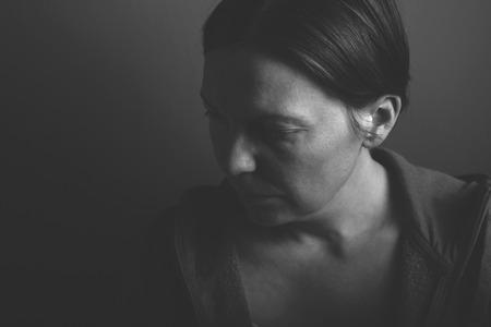 violencia: Mujer depresiva, bajo el retrato monocrom�tico clave de la triste mujer adulta en una habitaci�n oscura Foto de archivo