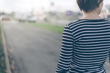 caminar: Imagen Mujer ordinaria desde atrás caminando por la calle vacía en otoño por la tarde, en tonos retro con enfoque selectivo Foto de archivo