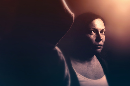 violent: Stalker concept, intense low key portrait of woman being stalked, retro toned image with selective focus