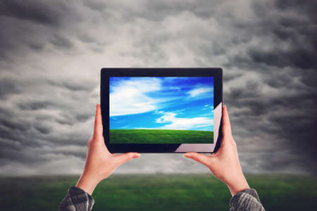 Environmentalist with digital tablet computer standing at open field