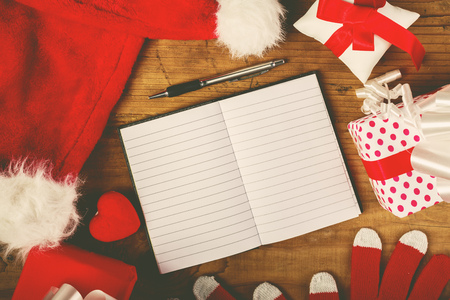 wish  list: Santa Claus work desk, empty notebook as copy space for good children wish list, hat and gloves with Christmas gifts and presents, top view