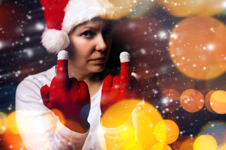 chrstmas: Chrstmas gift is late this year, young adult woman in Santa Claus costume showing middle finger, selective focus. Stock Photo