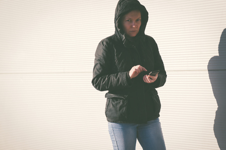 mobile telephone: Woman texting SMS message on mobile phone, female person in winter jacket using telephone outdoors, retro toned image with selective focus
