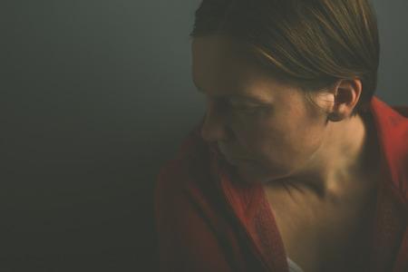 pointless: Depressive pessimistic lonely woman in dark room, low key portrait of sad adult female