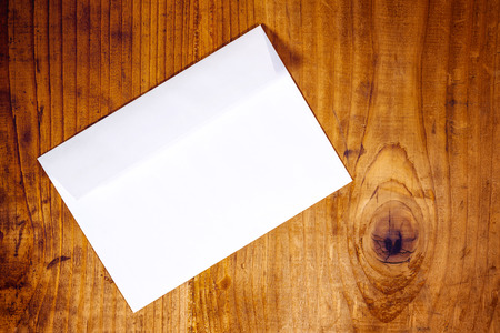 mail: Blank white envelope on wooden office desk, retro toned, top view