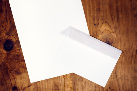 a4: Blank white envelope and letter paper on wooden office desk, retro toned, top view