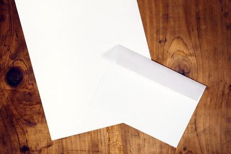 papier a lettre: enveloppe et lettre papier blanc vierge sur le bureau de bureau en bois, rétro tonique, vue de dessus