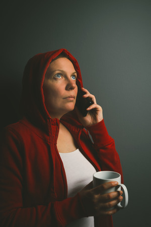 mobile voip: Beautiful red hooded woman drinking cup of coffee and using mobile phone in dark room, low key portrait