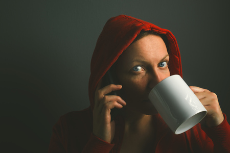 mobile voip: Beautiful red hooded woman talking on mobile phone and drinking cup of coffee in dark room, low key portrait Stock Photo