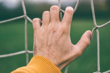 soccer net: Male hand holding soccer net, retro toned, selective focus Stock Photo