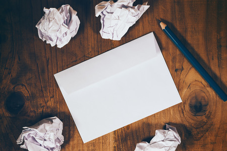 Blank white envelope, pencil and crumpled paper on wooden office desk, retro toned, top view Stock Photo